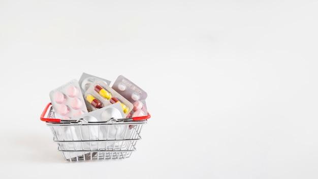 Cesta de alumínio cheia de muitos blister no fundo branco Foto Premium