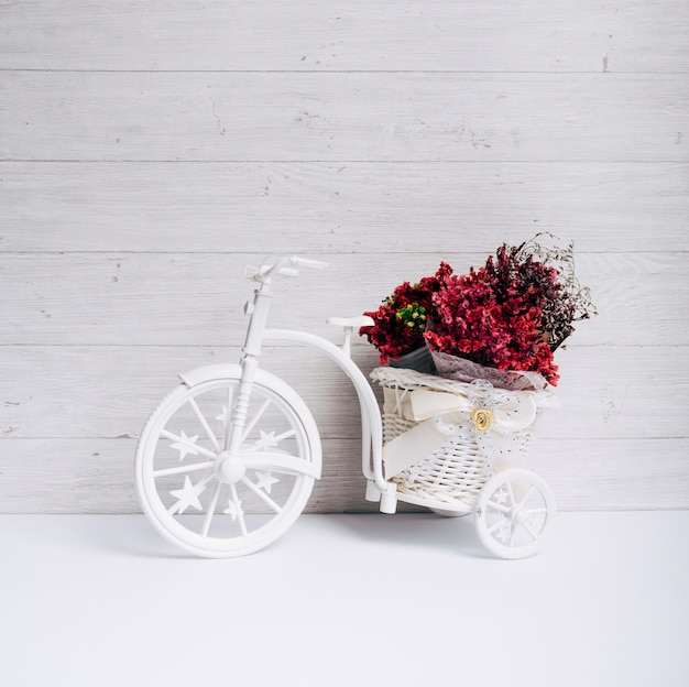Cesta de flores na bicicleta branca na mesa contra a parede de madeira Foto gratuita