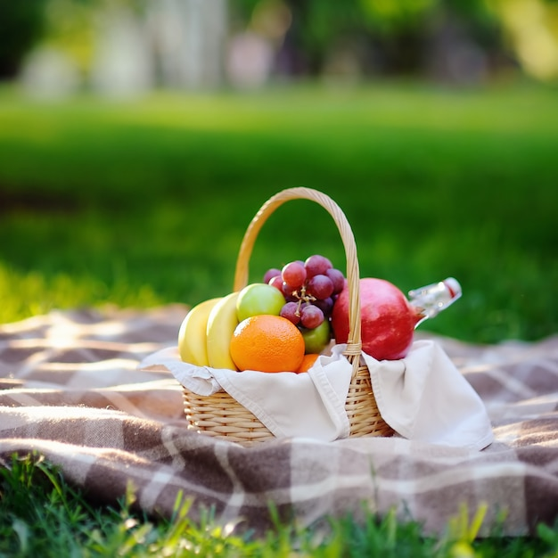 Cesta de piquenique com frutas, comida e água no frasco de vidro Foto Premium