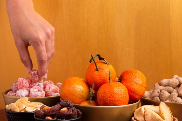 Cesta de tangerinas com iguarias do ano novo chinês Foto gratuita
