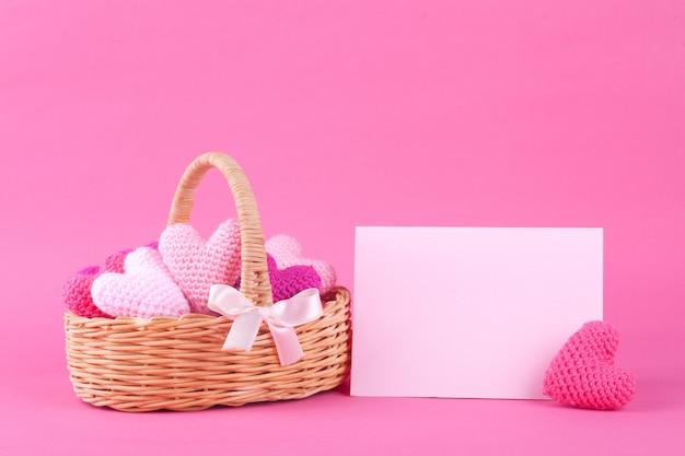 Cesta de vime com corações de malha multicoloridos. fundo rosa brilhante. decoração festiva. dia dos namorados. faça você mesmo Foto Premium
