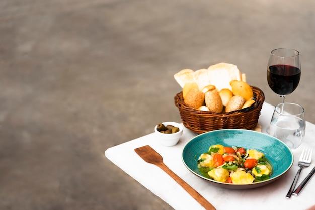 Cesta de vime de pão e massa de ravioli cozido na mesa branca Foto gratuita