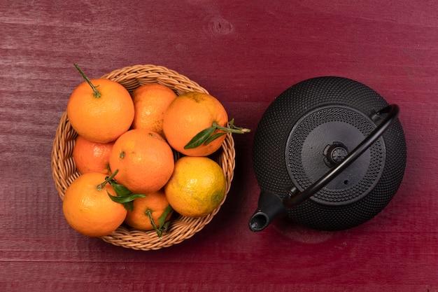 Cesta e bule de tangerina para o ano novo chinês Foto gratuita