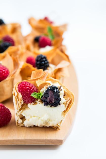 Cestas caseiras de pastelaria filo com creme mascarpone e bagas Foto Premium