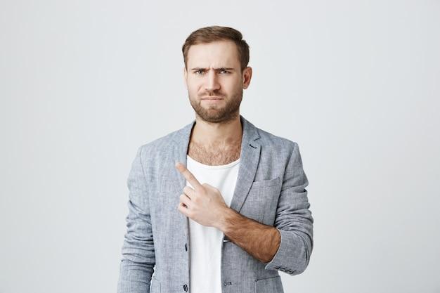 Cético homem barbudo descontente, apontando o canto superior esquerdo Foto gratuita