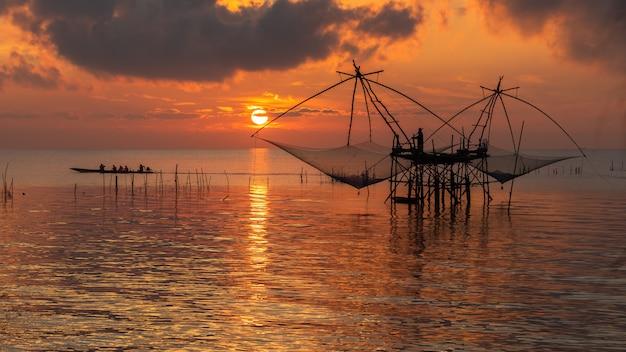 Céu amanhecer, com, pescador, ligado, quadrado mergulho, rede, e, turismo, bote, em, pakpra, vila, phatthalung, província, tailandia Foto Premium