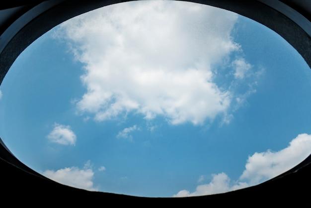 Céu azul nublado por uma janela Foto gratuita