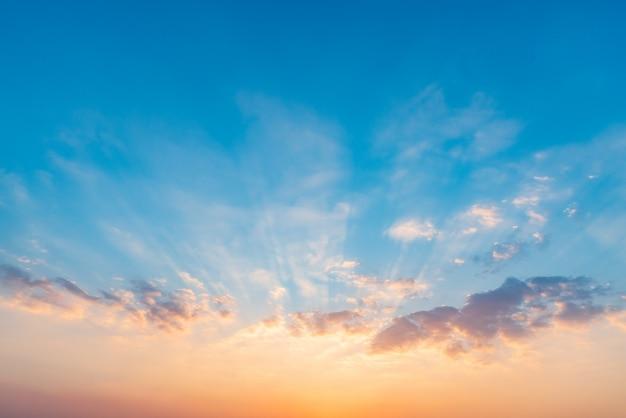Céu dramático bonito do por do sol com as nuvens coloridas alaranjadas e azuis. Foto Premium