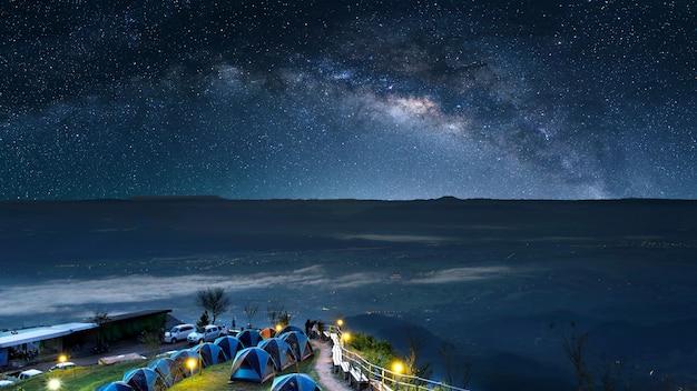 Céu estrelado à noite no alto das montanhas e uma tenda Foto Premium