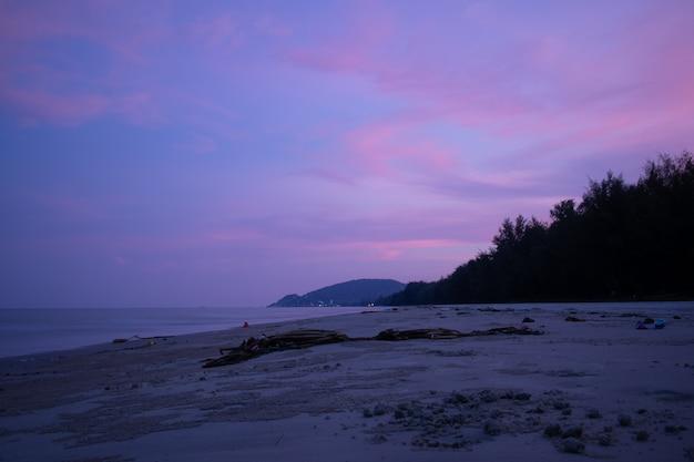 Céu roxo com feixe luminoso do por do sol na praia suja. Foto Premium