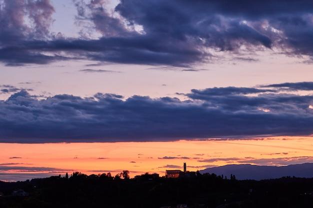 Céu vermelho do sol acima de conegliano Foto Premium