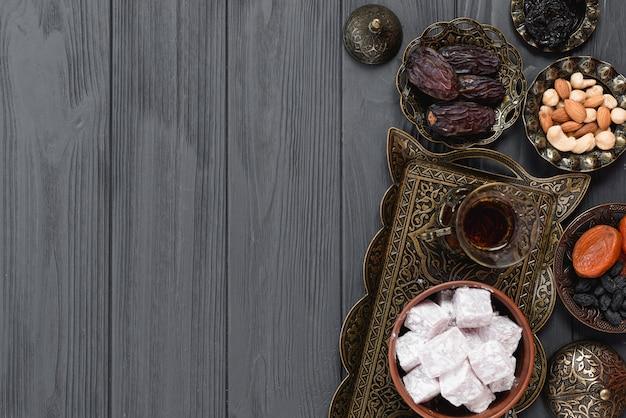Chá árabe tradicional do ramadã; lukum; frutos secos e nozes na prancha de madeira Foto Premium
