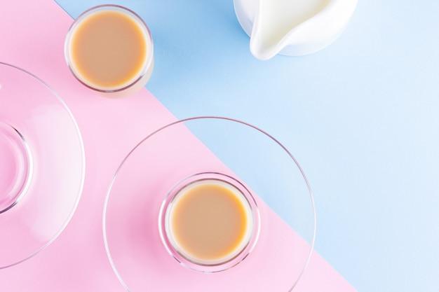 Chá com leite em um fundo rosa azulado. xícaras de chá turco e jarro de leite. xícara de chá preto inglês tradicional com leite. copie o espaço. vista do topo Foto Premium