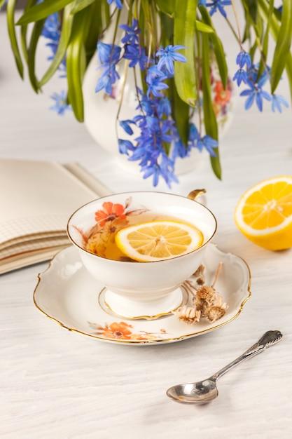 Chá com limão e buquê de prímulas azuis em cima da mesa Foto gratuita