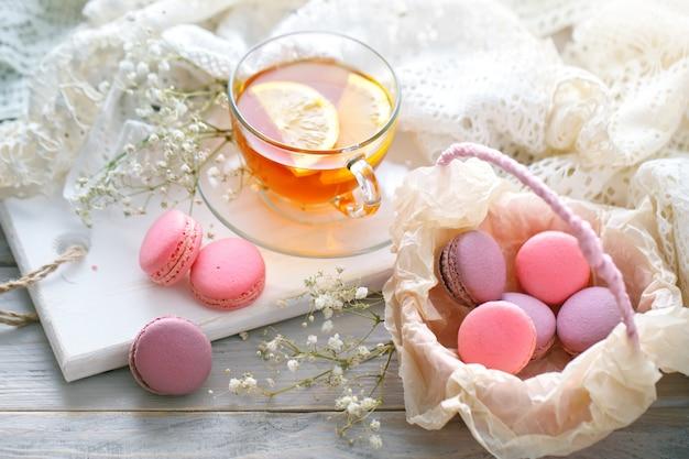 Chá com limão, flores silvestres e macaron na mesa de madeira branca. Foto Premium