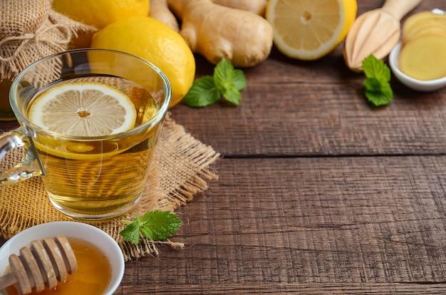 Chá da raiz do gengibre com limão e mel na tabela de madeira. Foto Premium
