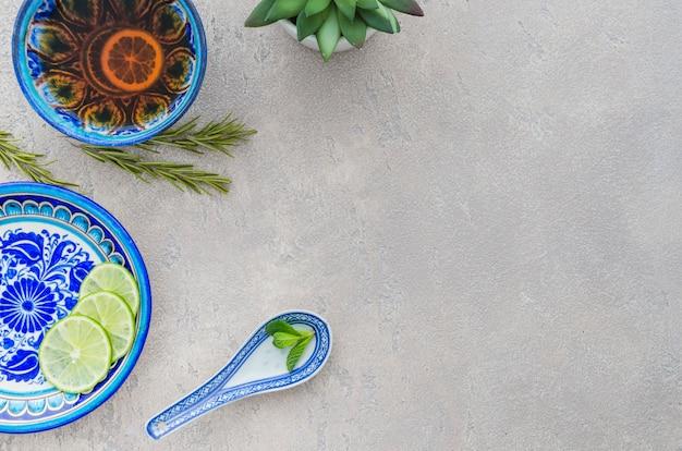 Chá de ervas caseiro feito com folhas de hortelã; fatias de limão; alecrim em pano de fundo concreto Foto gratuita