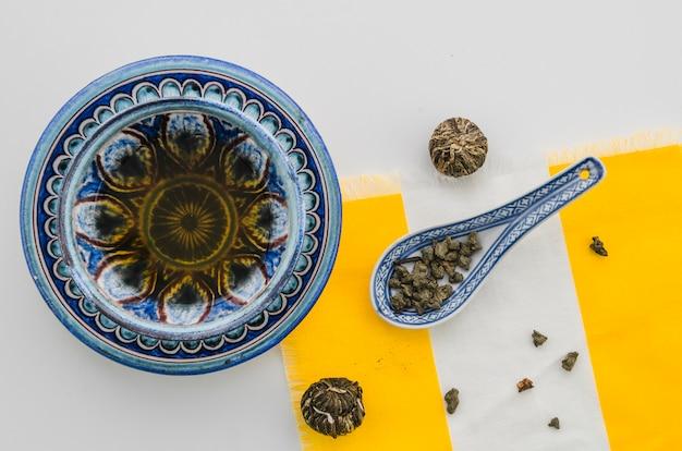 Chá de ervas com bola de chá floral desabrochando e poeira de chá oolong contra fundo branco Foto gratuita
