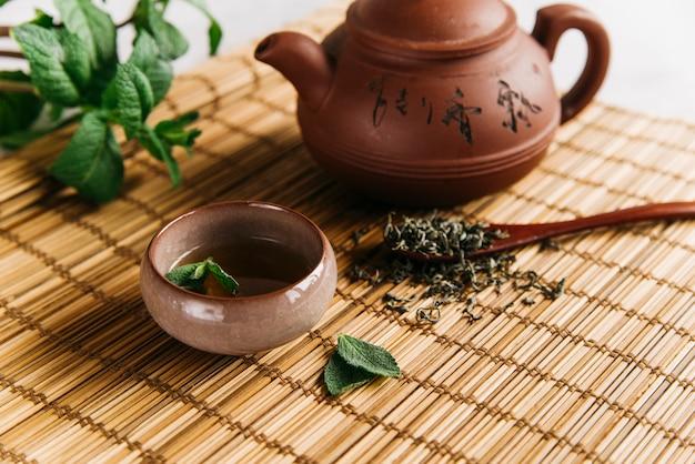 Chá de ervas com folhas de hortelã e ervas secas em placemat Foto gratuita