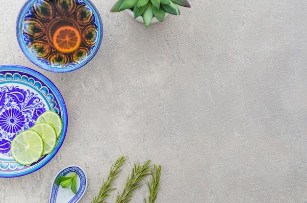 Chá de ervas feito com alecrim; fatias de limão; folhas de hortelã no pano de fundo texturizado cinza Foto gratuita