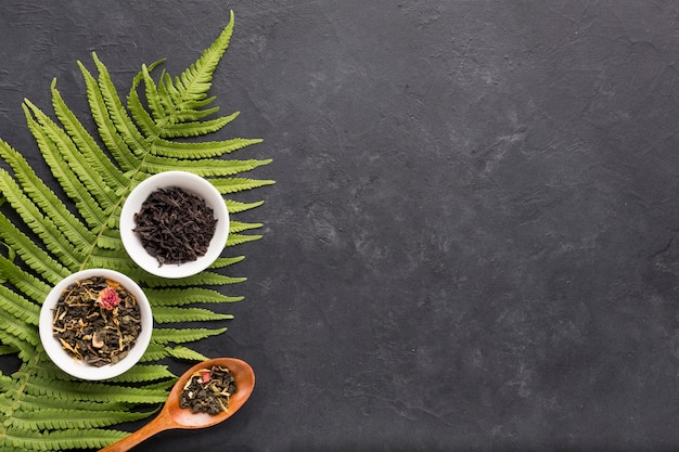 Chá de ervas secas em tigela de cerâmica branca com folhas de samambaia em fundo preto Foto gratuita