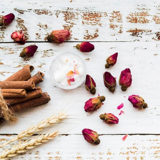 Chá de flores de botões de rosa; paus de canela; algodão em taça; feixe de espigas de trigo na prancha de madeira de textura branca Foto gratuita