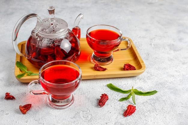 Chá de hibisco quente em uma caneca de vidro e bule de vidro. Foto gratuita