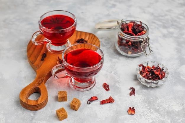 Chá de hibisco vermelho quente em uma caneca de vidro em concreto com pétalas de hibisco seco Foto gratuita