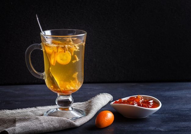 Chá de jasmim com kumquat em um copo de vidro em uma placa de madeira sobre um fundo preto Foto Premium