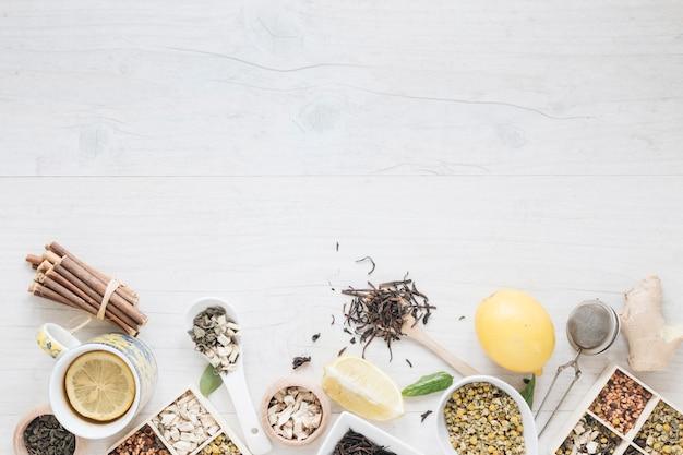 Chá de limão; ervas; filtro e gengibre organizar na mesa de madeira Foto gratuita
