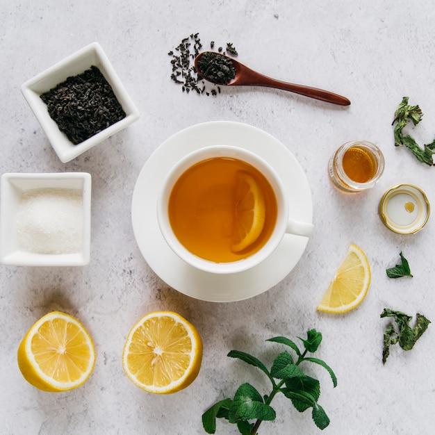 Chá de limão seco com açúcar; hortelã e mel no pano de fundo concreto Foto gratuita
