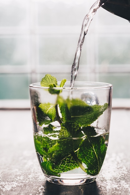 Chá de menta fresca perto da janela. casa ou saúde aconchegante Foto Premium