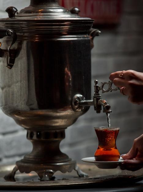 Chá de samovar tradicional colocando em vidro Foto gratuita