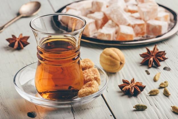 Chá em copo árabe com delícia turca rahat lokum e diferentes especiarias sobre superfície de madeira Foto Premium