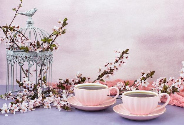 Chá em xícaras cor de rosa e flores de cerejeira em uma gaiola decorativa Foto Premium