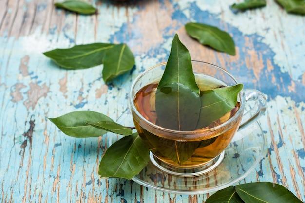 Chá fresco de folha de louro em um copo em uma mesa rústica de madeira Foto Premium