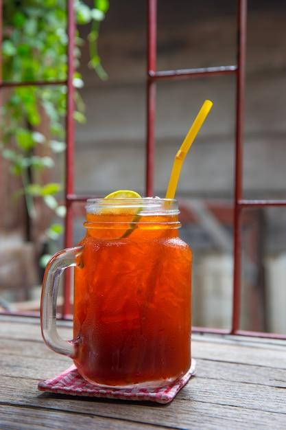 Chá gelado de limão na mesa vitage em um jarro Foto Premium