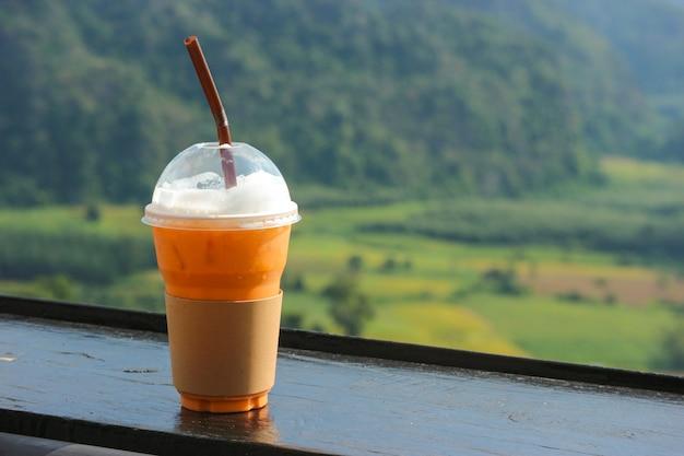Chá gelado tailandês no copo plástico com vista natual como o fundo. Foto Premium