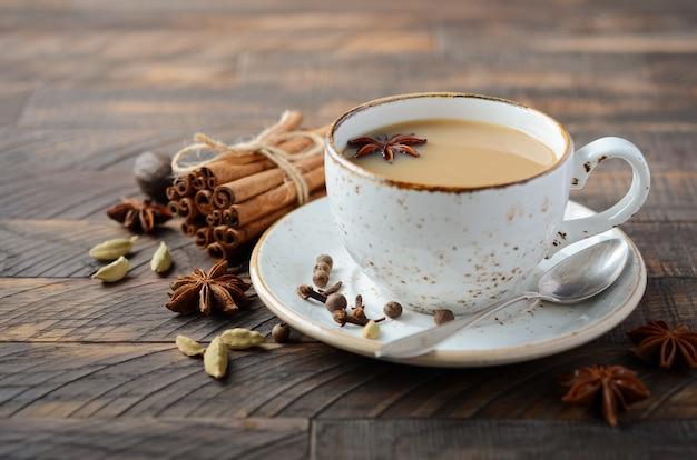 Chá indiano masala chai. chá temperado com leite no escuro de madeira Foto Premium