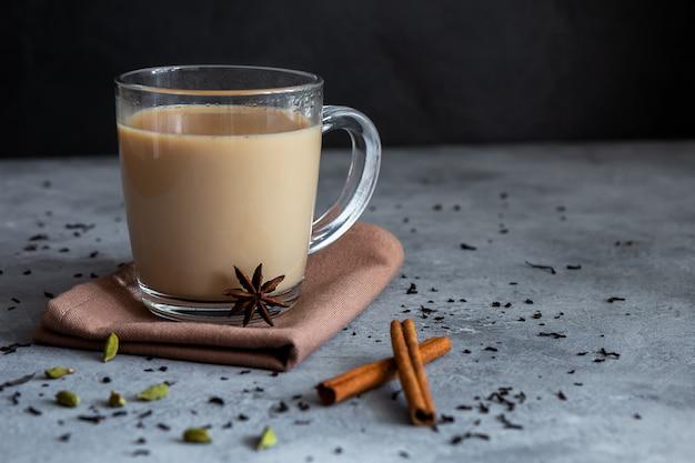 Chá indiano masala chai com especiarias em uma caneca de vidro Foto Premium