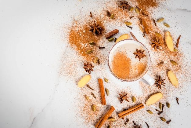 Chá indiano tradicional do masala chai com especiarias - canela, cardamomo, anis, branco. vista superior copyspace Foto Premium