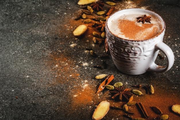 Chá indiano tradicional do masala chai com especiarias canela, cardamomo, anis, pedra escura. Foto Premium