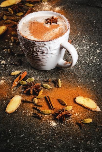 Chá indiano tradicional masala chai com especiarias - canela, cardamomo, anis Foto Premium