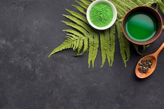 Chá jogo verde e erva seca com folhas de samambaia no fundo preto texturizado Foto gratuita