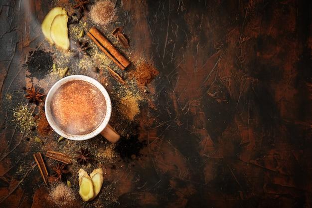 Chá masala com canela e anis em uma mesa de barro. uma xícara de chá masala com especiarias, sobre um fundo de concreto. vista do topo. Foto Premium