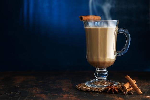 Chá masala com canela e badian em uma mesa de barro. um copo de chá masala, sobre um fundo azul. Foto Premium