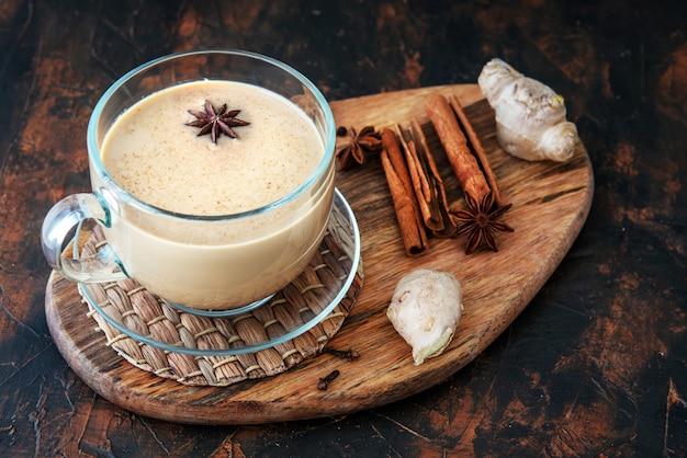 Chá masala em uma mesa de barro com especiarias. vista do topo Foto Premium
