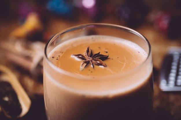 Chá masala (masala chai). uma bebida quente tradicional na índia e no sul da ásia. chá preto com leite e especiarias Foto Premium