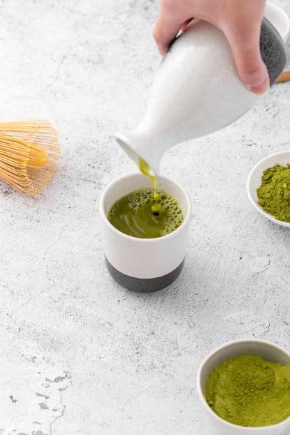 Chá matcha de close-up, despejando copo Foto gratuita