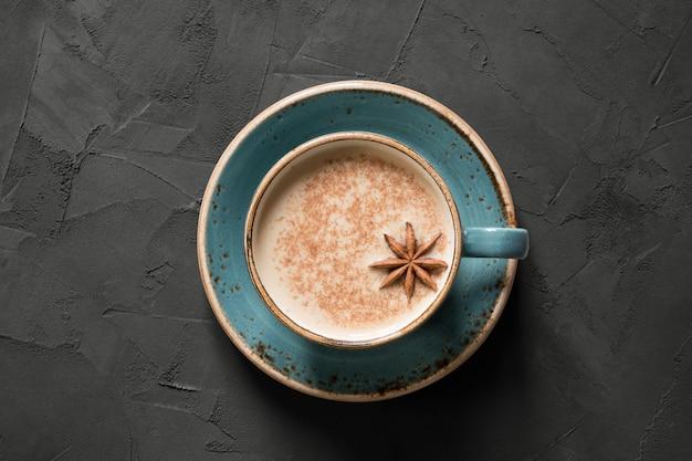 Chá ou café indiano de masala no copo azul com especiarias e canela no preto. vista do topo. Foto Premium